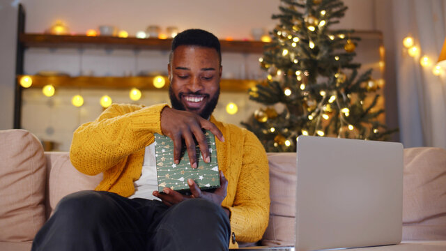 Young african man sitting on couch and opening christmas present having online chat on laptop