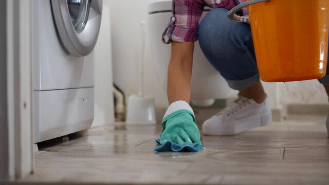 Woman in gloves having washing machine leak wiping floor and wrinkling rag in bucket