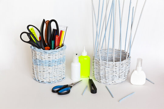 Process weaving a decorative basket of twisted paper tubes on a white background. Glue, awl and scissors for work nearby with a finished basket with tools. Crafts and hobby concept
