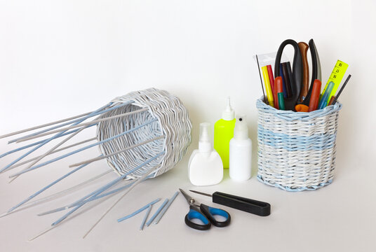 Weaving a basket of twisted paper tubes for a gift. Glue, awl and scissors for work nearby with a finished basket with tools. Crafts and hobby concept. White background, free space for text