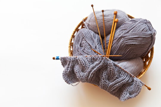 Basket with needlework on a white background. Balls of gray woolen and mohair yarn, wooden knitting needles and a started knitted warm scarf. Needlework cocept. Flat lay, copy space, top view, mock up