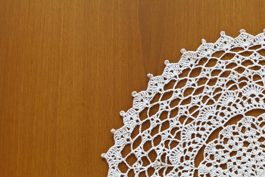 Fragment of a lace napkin from natural cotton yarn, crocheted by hand on a wooden table. Crochet as a hobby. Handicraft background. Flat lay, copy space, close-up, top view, mock up