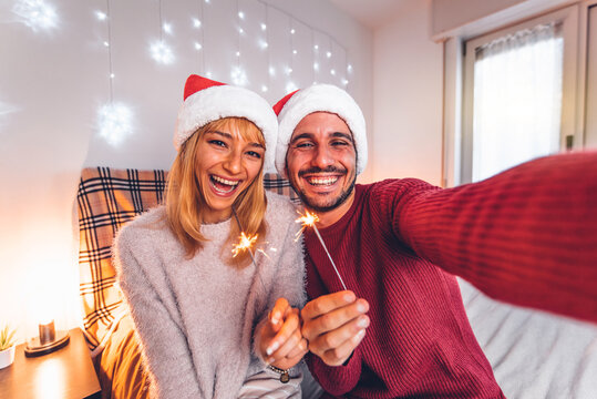 Happy couple taking selfie celebrating Christmas time at home -  Winter holiday concept with young friends having fun