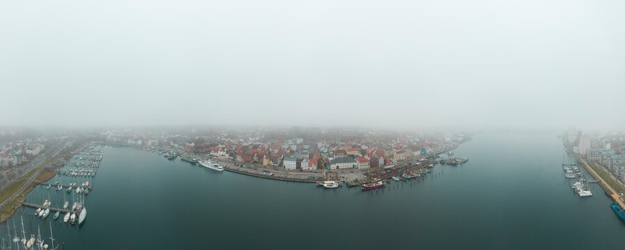 Drone aerial panorama of Flensburg Germany foggy mood
