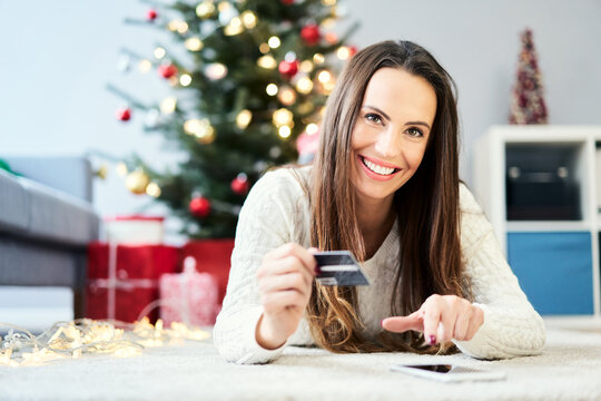 Photo of woman paying for christmas shopping with credit card online