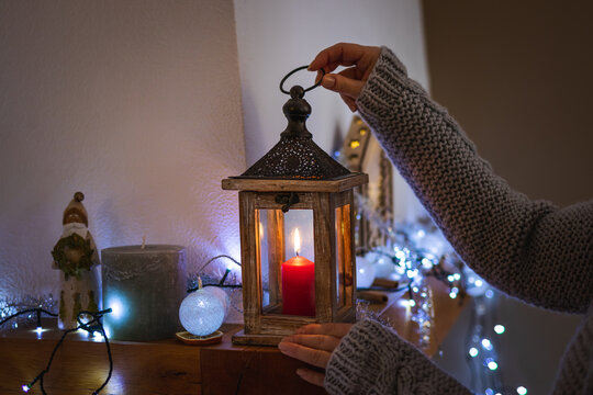 Woman preparing christmas decoration with lantern and lights in cozy home interior