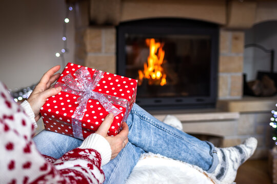 Woman holding christmas gift box in hands near fireplace in cozy home interior. Woman sitting at chair and opening christmas present