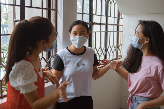 Three girls in face masks having a lively chat indoors. Best friends during new normal.