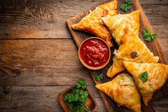 Samsa or samosas with meat and vegetables with tomato sauce on wooden background. Traditional asian food. Top view.