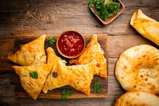 Samsa or samosas with meat or vegetables, doner kebab and pita with tomato sauce on wooden background. Traditional asian food. Top view.
