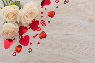 Bunch of white roses and red hearts lying on wooden background