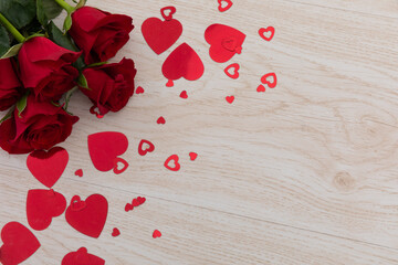 Bunch of red roses and red hearts lying on wooden background