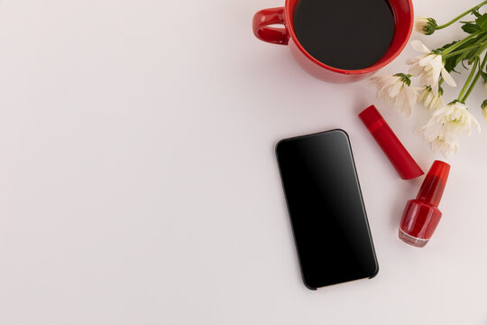 Smartphone, red lipstick, nail varnish, coffee and flowers on white background