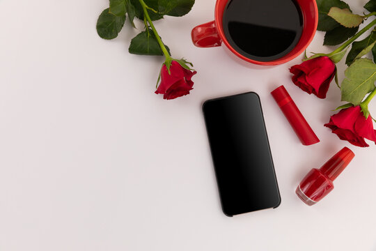 Smartphone, red lipstick, nail varnish, coffee and roses on white background