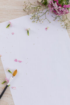 White paper with paintbrush, flowers and petals on wooden background
