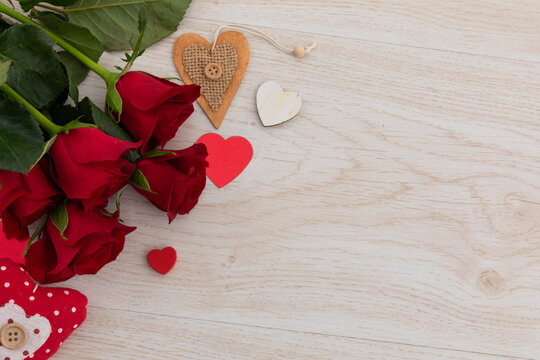 Bunch of red roses and hearts lying on wooden background