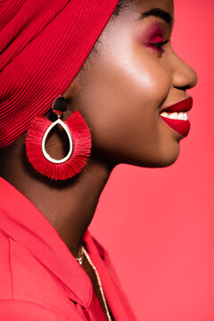 profile of african american young woman in stylish outfit and turban isolated on red