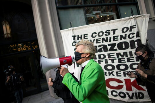 """Anti-shopping performance artist who goes by the name Reverend Talen of the Church of Stop Shopping participates in a protest called """"Make Amazon Pay"""", at the building where Bezos lives in Manhattan, New York"""