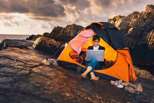 Female sitting in the tent and working on computer. Business woman working from the beach. Working from distance concept. Freelancer travel and work online.