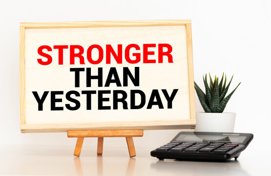 stronger than yesterday white chalk text on a vintage slate blackboard