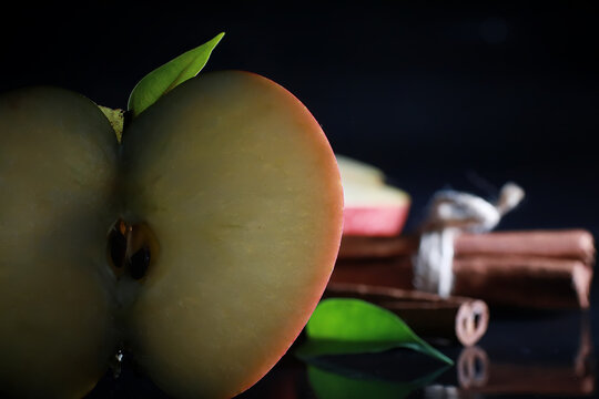 Composition with apple slices on a black background. A slice of apple with back light on a black background with water drops. Juicy apple on a table.
