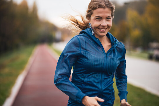 Beautiful adult woman is jogging outdoor on cloudy day in autumn.