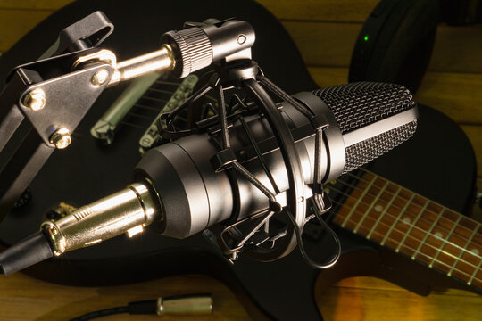 Condenser microphone on the background of an electric guitar