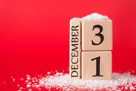 The last day of year concept. Close up photo of wooden cubes calendar showing the last date of year isolated on red background with snow