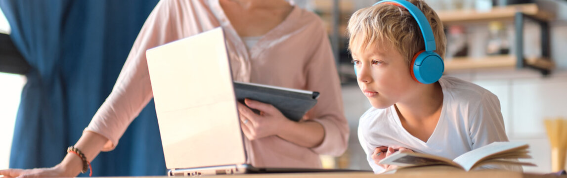 mom helping young son with laptop to do homework. Young woman teaching little boy to use the computer. baby sitter teaching little child girl use laptop application.