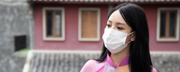 Banner of young Asian Vietnamese woman properly wearing face mask in outdoor public space