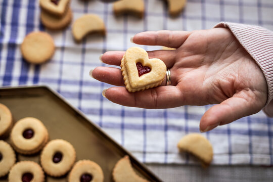 Baked Linzer cookie in hand. Homemade traditional christmas sweet food