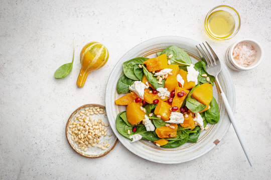 Salad with roasted pumpkin, cheese, spinach, Pine nuts and seasonings on white background, top view