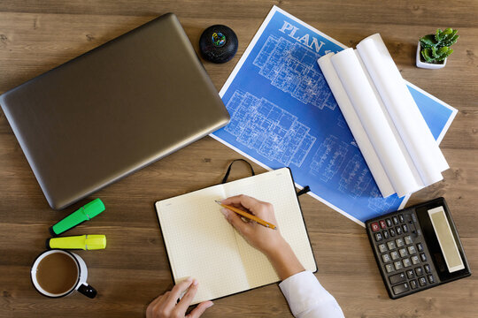 Female hand in a shirt writes in a leather notebook. Computer, cup of coffee, graphics, drawings, calculator on the table in the office. Business and Finance.