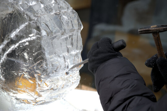 Sculptors at work chisling designs into large blocks of ice.