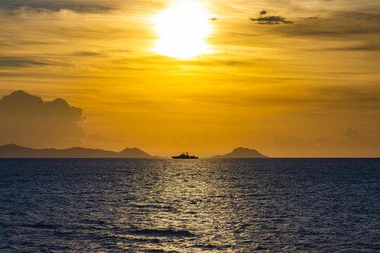 Schiff am Horizont zwischen Insel und Festland vor der aufgehenden Sonne