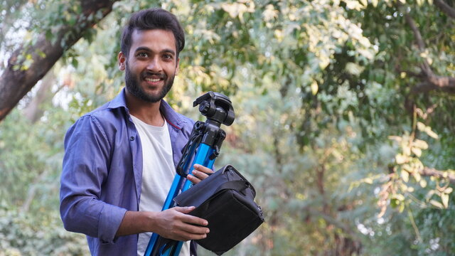 Professional photographer. Portrait of confident young man in shirt holding hand on camera on tripod