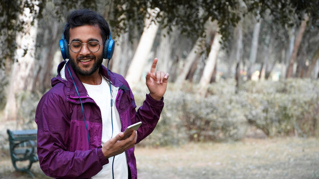 Happy young handsome Indian man wearing headphones listening to music from smartphone in the city