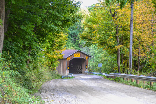 Covered bridge  on a country road  surrounded by colorful fall leaves in Ashtabula, Ohio.