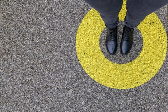 Black shoes standing in yellow circle on the asphalt concrete floor. Comfort zone or frame concept. Feet standing inside comfort zone circle. Place for text, banner