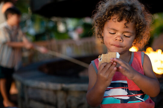 Cute little boy about to eat a s`more while sitting by an outdoor fire. Young black boy enjoying s`mores by the campfire at night in the summer time.
