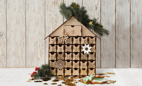 Wooden house shaped advent calendar, Christmas cookies and festive decor on white table