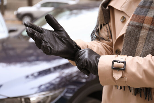 Stylish man putting on black leather gloves outdoors, closeup
