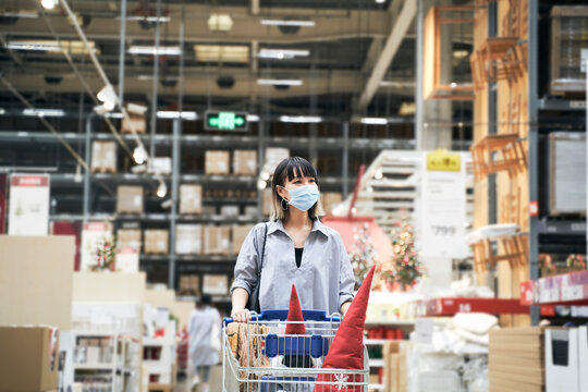 Asian woman wearing face mask push shopping cart in warehouse store buying Christmas decorations & gifts