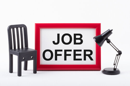Text JOB OFFER in red frame next to a miniature chair and lamp on white background. Business concept.