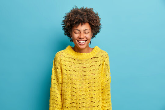 Portrait of overjoyed gentle dark skinned woman smiles broadly closes eyes and shows white teeth wears casual yellow knitted jumper expresses positive emotions isolated over blue background.