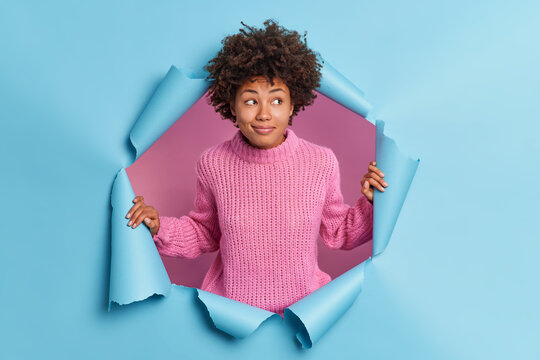 Curious dark skinned young woman looks with interest aside looks gladfully wears warm knitted sweater poses through hole of paper background concentrated at something pleasant has pleased smile
