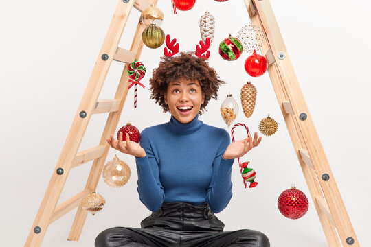 Pleased dark skinned woman with curly hair looks above raises palms enjoys decorating room for Christmas holidays dressed casually poses on floor against New Year toys uses ladder to decorate fir tree