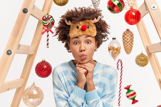 Headshot of beautiful woman keeps hands under chin lips folded wears sleep mask and nightwear enjoys cozy domestic atmosphere decorates room for New Year party uses toys and ladder. Holidays concept