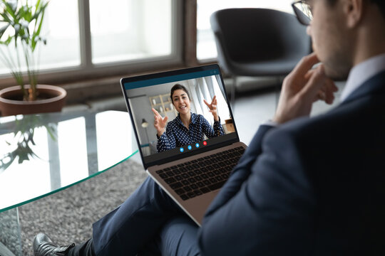 Thoughtful young male employee connecting with indian female colleague by video link using laptop, pensive businessman making conference call to mixed race woman consultant to get her recommendations