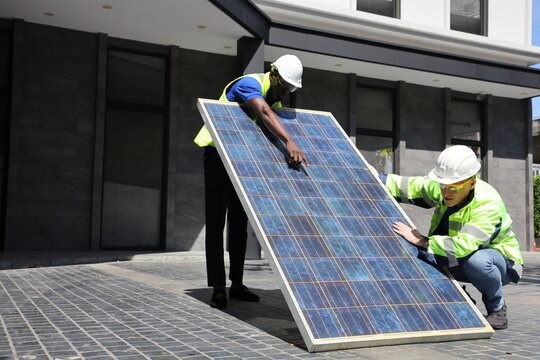 Caucasian and African American workers working on installing solar panel on the rooftop of the house for renewable energy and environmental friendly outcome concept